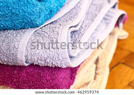 Colorful towels: purple, white, grey, blue. macro focus detail close up. Wooden panels floor