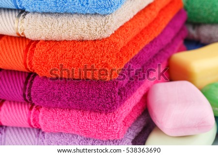 Colorful towels stacks and soaps closeup picture.