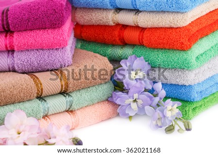 Colorful towels stacks with flowers closeup picture. - stock photo