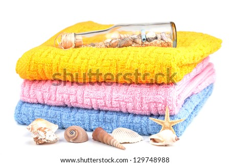colorful towels with shells on white background