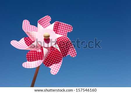 Colorful toy pinwheel against clear blue sky background  - stock photo