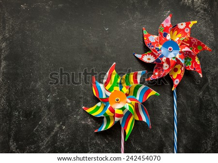 Colorful toy windmills on black chalkboard from above. Background layout with free text space. - stock photo