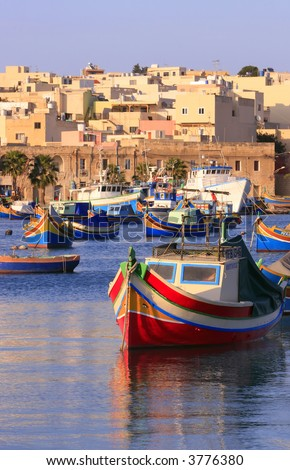 Colorful, traditional fishing boats against the backdrop of Marsaxlokk village in the mediterranean island of Malta. Copyspace at the bottom and top. See portfolio for more. - stock photo