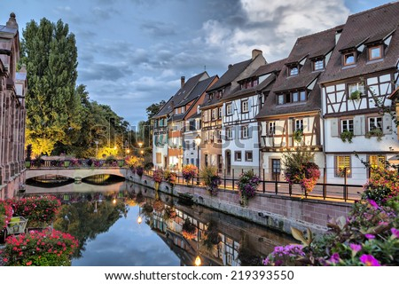 Colorful traditional french houses on the side of river Lauch at the evening in Colmar, France - stock photo