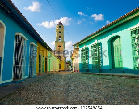 Colorful traditional houses and old church in the colonial town of Trinidad in Cuba - stock photo