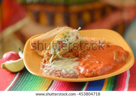 Colorful Traditional Mexican food dishes combo plate of taco, tamale and chicken - stock photo
