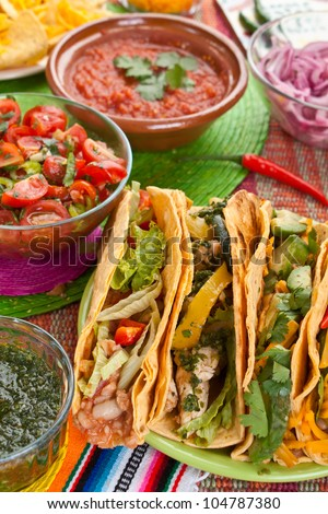 Colorful Traditional Mexican food dishes: various fajitas, nachos, salsa verde, tomato salsa, salsa cruda served on a beautifully decorated table - stock photo