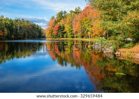 Colorful tree reflections in pond water on a sunny autumn day in New England - stock photo