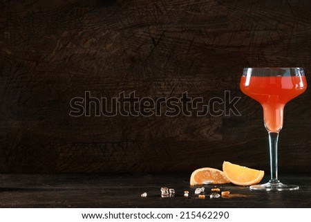 Colorful tropical orange and red rum or tequila cocktail served in a stylish tall glass on a dark counter top with copyspace for your Christmas, New Year or festive party greeting on a dark background - stock photo