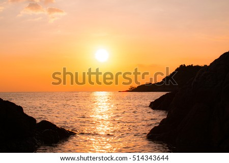 Colorful tropical sunset with silhouette stone