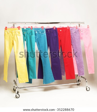 colorful trousers on a hanger isolated with shadows - stock photo