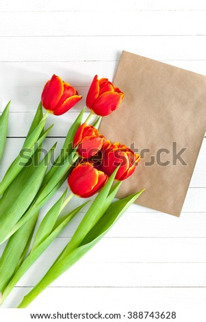 Colorful tulip bouquet and blank greeting card. Top view over white wooden table