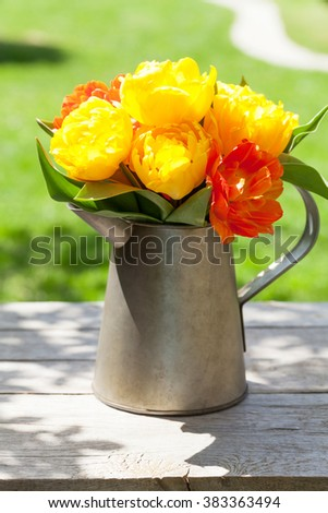 Colorful tulips bouquet in watering can on sunny garden table - stock photo