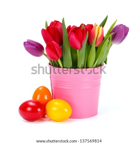 Colorful tulips in pink bucket and three painted Easter eggs