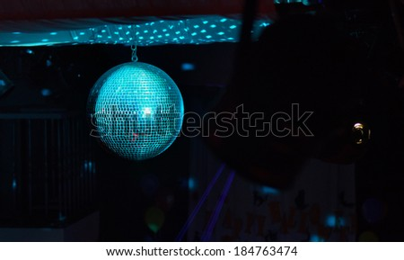Colorful turquoise blue mirrored metallic disco ball in a nightclub hanging in the darkness with copyspace - stock photo