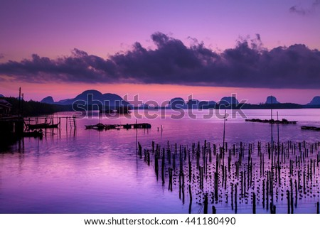 Colorful twilight in morning over seascape at fisherman village and The Oyster Farms at Fisherman village at Samchong-tai, Phang Nga, Thailand - stock photo