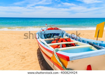 Colorful typical fishing boat on beach in Armacao de Pera coastal village, Portugal - stock photo