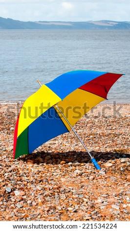 colorful umbrella at a pebble beach - stock photo