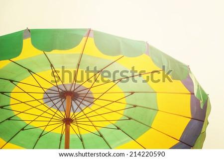 Colorful Umbrella Beach on sunny summer day, toned - stock photo