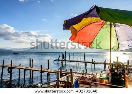 Colorful umbrella on iced slushie vendor cart in evening light at Lake Atitlan with San Pedro volcano behind in Guatemalan highlands. - stock photo