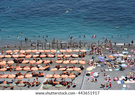 Colorful umbrellas and a stone beach in Positano, Italy, on the Amalfi Coast in Italy.