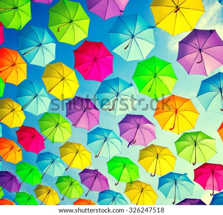 Colorful umbrellas background. Colourful umbrellas urban street decoration. Hanging Multicoloured umbrellas over blue sky. Bright Colors backdrop - stock photo