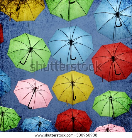 Colorful umbrellas floating magically in the moody sky. Image done on old paper texture. Real objects with paper texture design background - stock photo