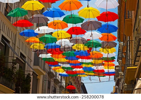 Colorful umbrellas installed on the street in Spanish city. Urban sun protection with umbrellas at work.  - stock photo