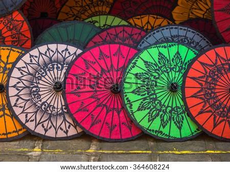 Colorful umbrellas on street market in Bagan, Myanmar. - stock photo