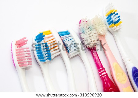 Colorful used toothbrushes on the white background. - stock photo