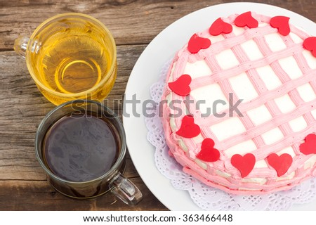 Colorful vanilla cake decorate with cream butter and chocolate in red heart shape. On white plate and over wooden table. With glass of tea and hot coffee. Top view. - stock photo