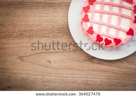 Colorful vanilla cake decorate with cream butter and chocolate in red heart shape. On white plate and over wooden table.  Top view. Dark vignette. - stock photo