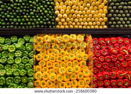 Colorful variety of market vegetables including bell peppers, cucumbers and squash - stock photo