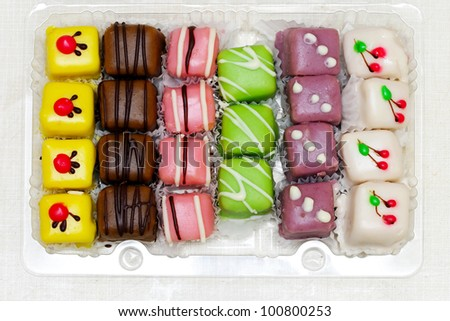 Colorful variety of mignon cakes in the box