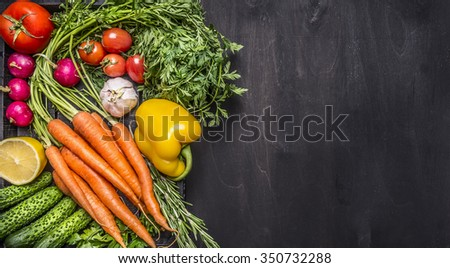 Colorful various organic farm vegetables carrots cherry tomatoes, garlic, cucumber, lemon, pepper, radish, wooden spoon salt pepper colored, oil wooden rustic background top view  border, place text - stock photo