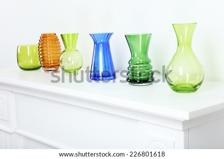 Colorful vases on white table, close-up - stock photo