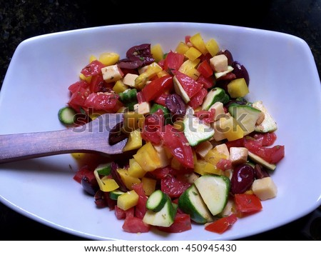 Colorful Vegetable and Gouda Salad - a healthy summer vegetable salad with tomato, bell pepper,  zucchini, kalamata olives, and gouda cheese, in a white bowl with a wooden serving fork - stock photo
