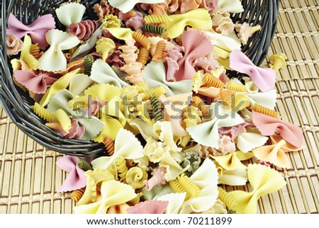 Colorful vegetable pasta spilling out of a basket, textured background - stock photo