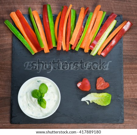 "Colorful vegetable sticks with a spicy dip on a slate plate with the note ""Enjoy your food"" - stock photo"