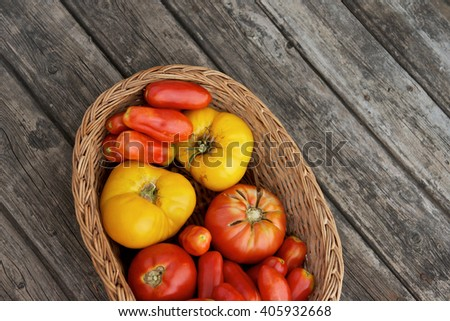 Colorful vegetables/A basket of fresh tomatoes/Different types of tomatoes on a wooden board - stock photo