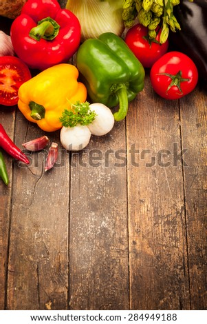 Colorful vegetables over old wooden table - stock photo