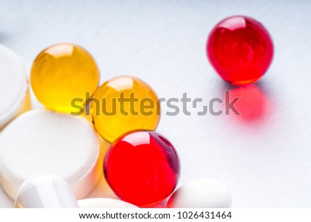 Colorful vitamin pills, medicine tablets and capsules on an abstract white background. Healthcare, medical and pharmaceutical concept. Detailed closeup studio shot with soft selective focus.
