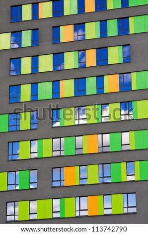 colorful wall of the building with reflective windows in the sky - stock photo