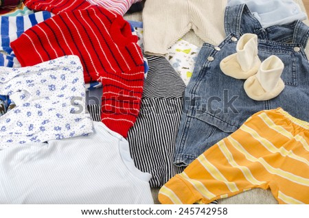 Colorful wardrobe of newborn,kids, babies full of all clothes, shoes,accessories and toys - stock photo