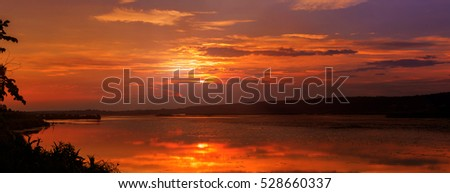 Colorful warm sunset over the evening lake. clouds on the sky reflected in water. Artistic style. creative images. majestic, wonderful landscape. beauty of the world