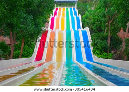 Colorful water slides in tropical aqua park - stock photo