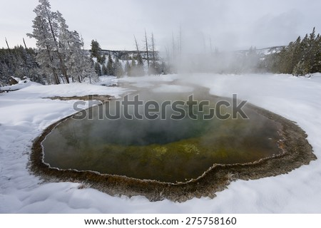 Colorful waters of a geyser basin in a snow-covered landscape. Yellowstone National Park. - stock photo