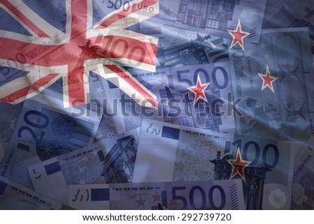 colorful waving new zealand flag on a euro money background - stock photo