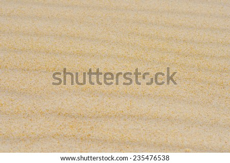 Colorful wavy and rippled lines and curves on sandy desert or beach dune, remote and barren, natural design texture backdrop, background or wallpaper. - stock photo