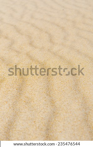 Colorful wavy and rippled lines and curves on sandy desert or beach dune, remote and barren, natural design backdrop, background or wallpaper. - stock photo